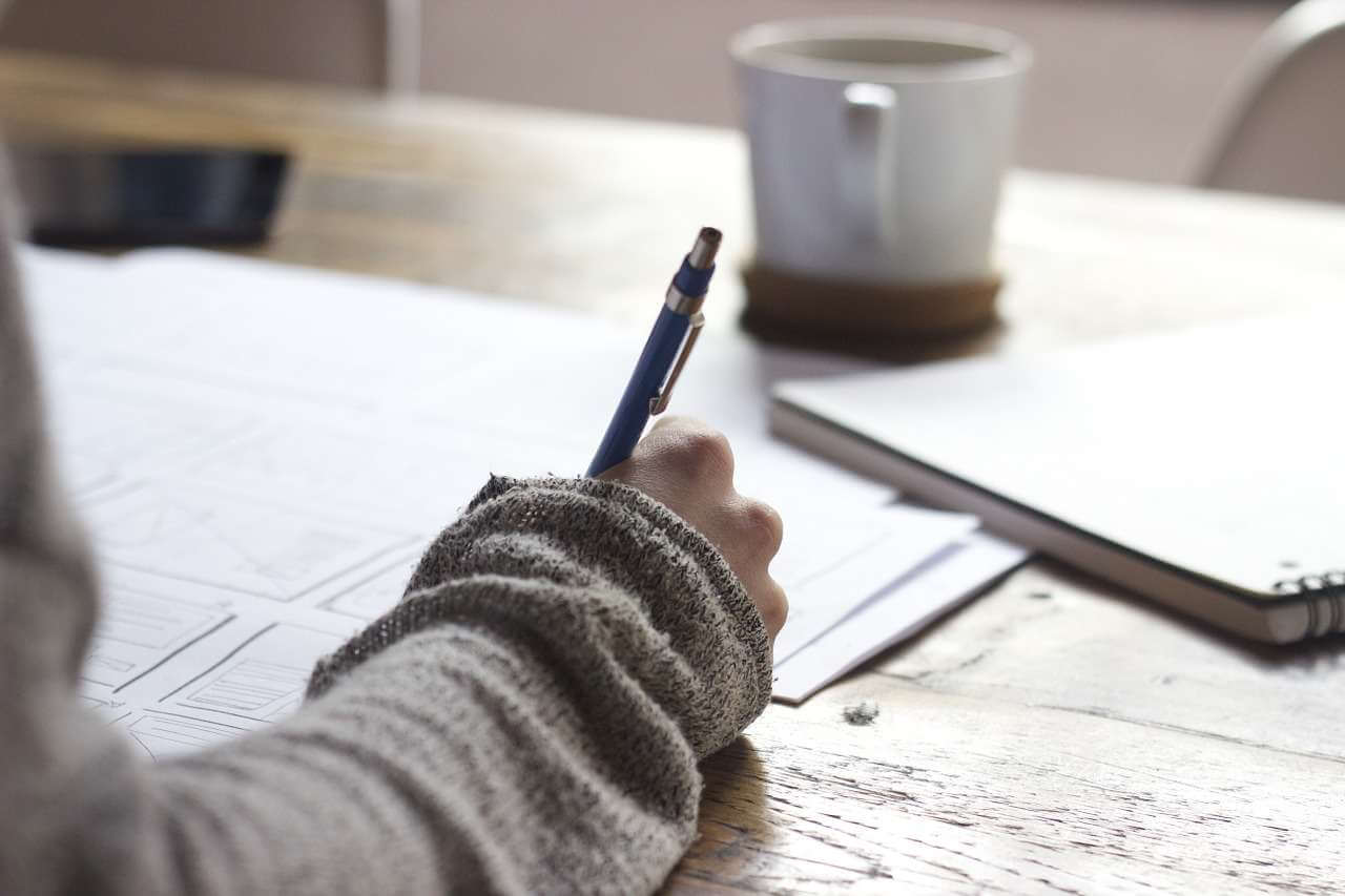 a woman hand writing something, a cup and a notebook on the table
